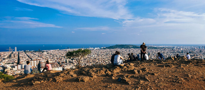 Photo of several people on a rocky hilltop overlooking a large city on the ocean coast.