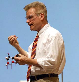A photo of Dr. John Dolhun, the course instructor, lecturing and holding a molecular model.