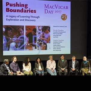 8 panelists sit on stage in front of a the title 'Pushing Boundaries' at MacVicar Day 2017.